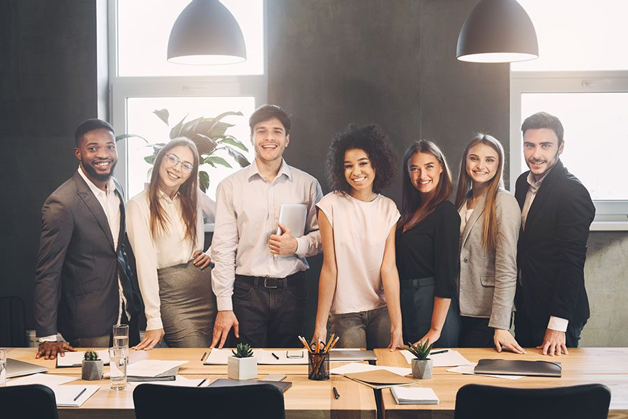Employee Benefits - Portrait of a Group of Smiling Diverse Employees Standing in the Office Next to a Conference Table