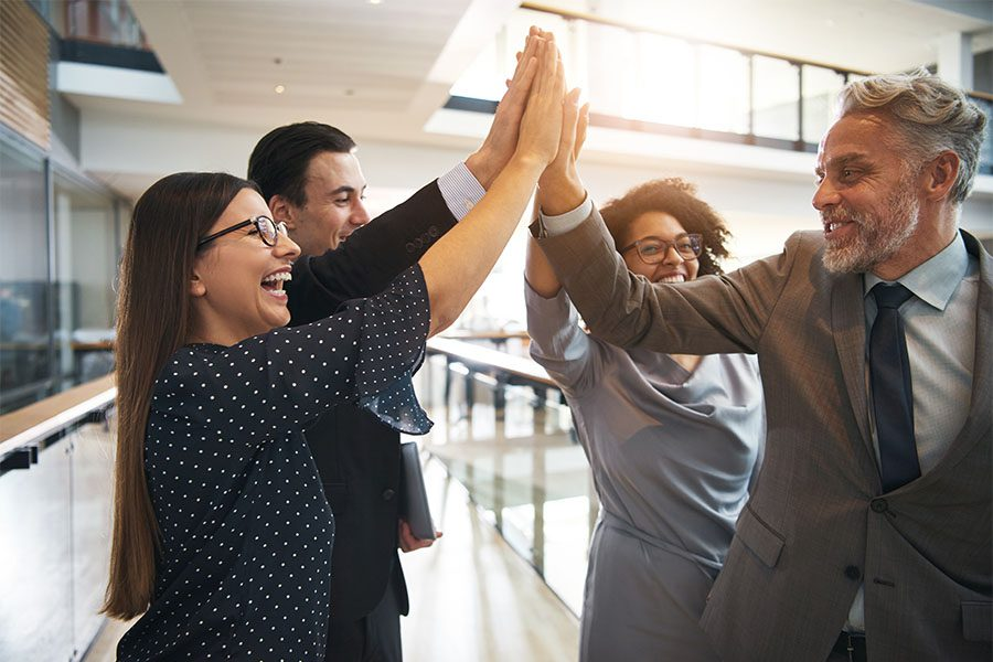 About KBP - Group of Cheerful Employees Celebrating Success By Giving Each Other High Fives