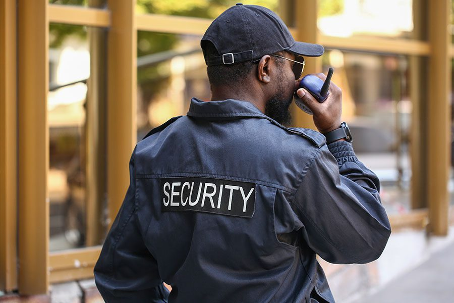 Security Guard Insurance - Security Guard Talking into the Radio While Watching Outside a Building