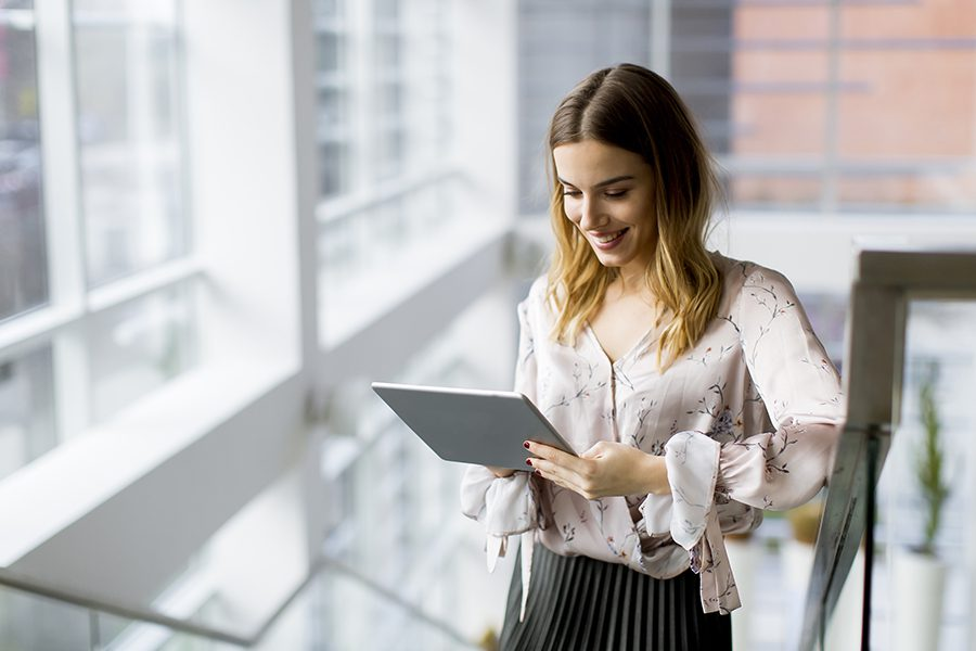 Client Center - Businesswoman Using a Tablet While Standing on the Stairs in the Office