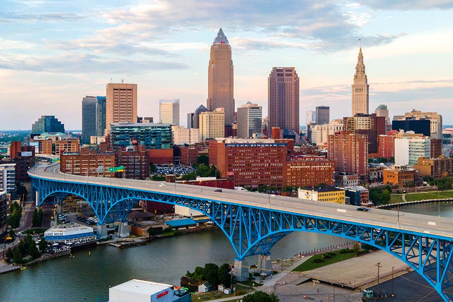 Cleveland OH - Aerial View of Downtown Cleveland Ohio Next to the River with Bridge and a Sunset Sky