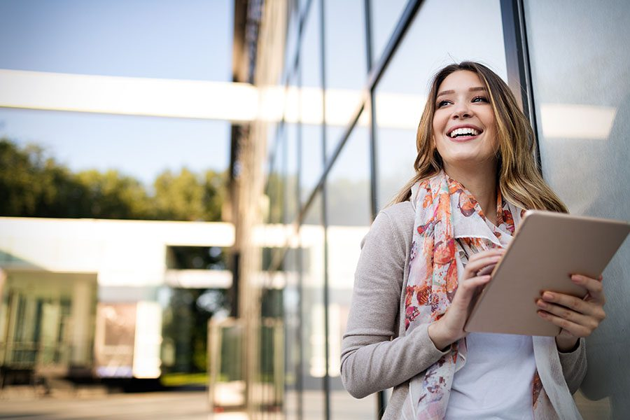 Client Center - Closeup View of Smiling Business Woman Standing Next to a Modern Office Building Using a Tablet