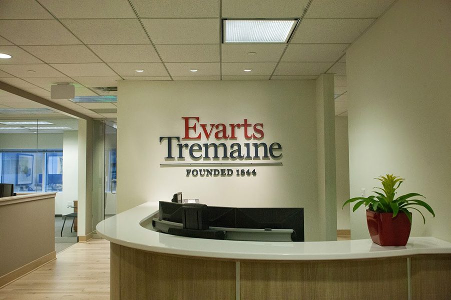 Contact - View of Front Entrance of Evarts Tremaine Office with Logo on the Wall and Rows of Computers Behind Front Desk