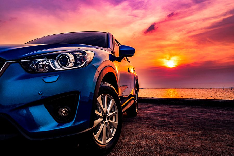 Auto Insurance - View of a Blue Compact SUV Car Parked on a Concrete Road by the Ocean at Sunset