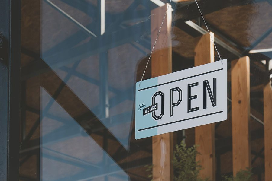 Business Owners Insurance - We Are Open Sign Hanging on the Entrance Door of a Small Cafe in the City