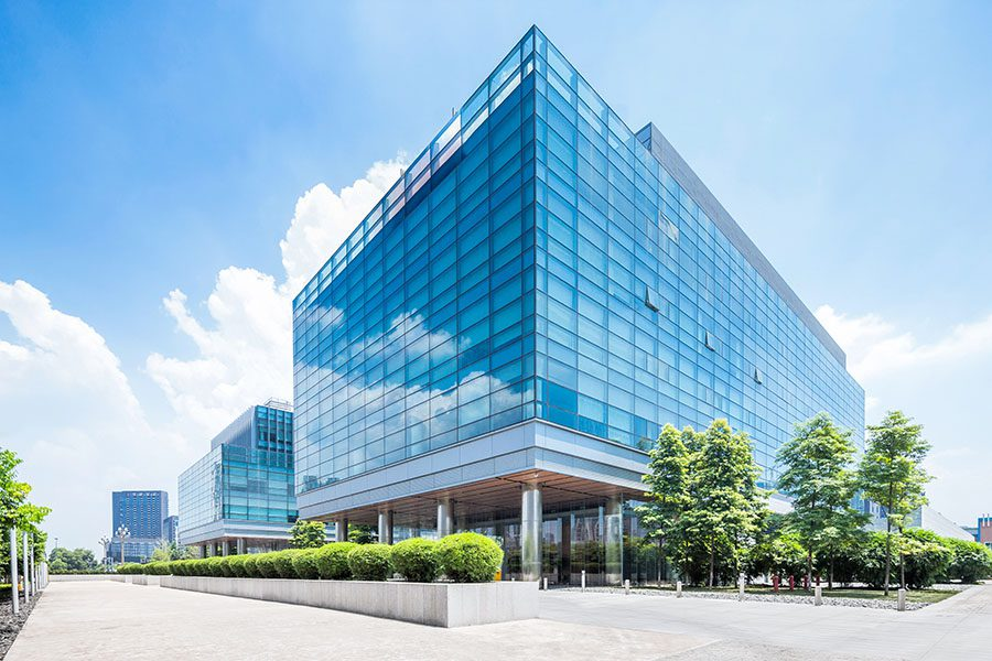 Commercial Property Insurance - View of Modern Glass Commercial Office Building Exterior with Green Landscaping Against a Bright Blue Sky