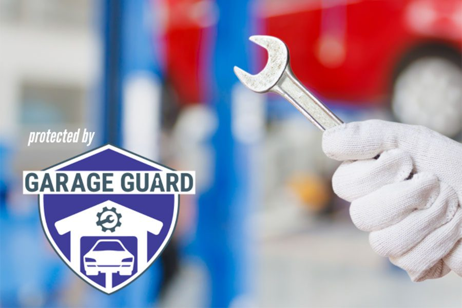 Garage Repair Shop Insurance - Blurred Photo of a Mechanic Inside a Garage Repair Shop Holding a Wrench with a Garage Guard Logo on the Left Side