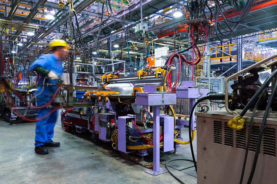 General Liability Insurance - View of a Factory Worker Working Inside a Modern Automatic Automobile Manufacturing Facility