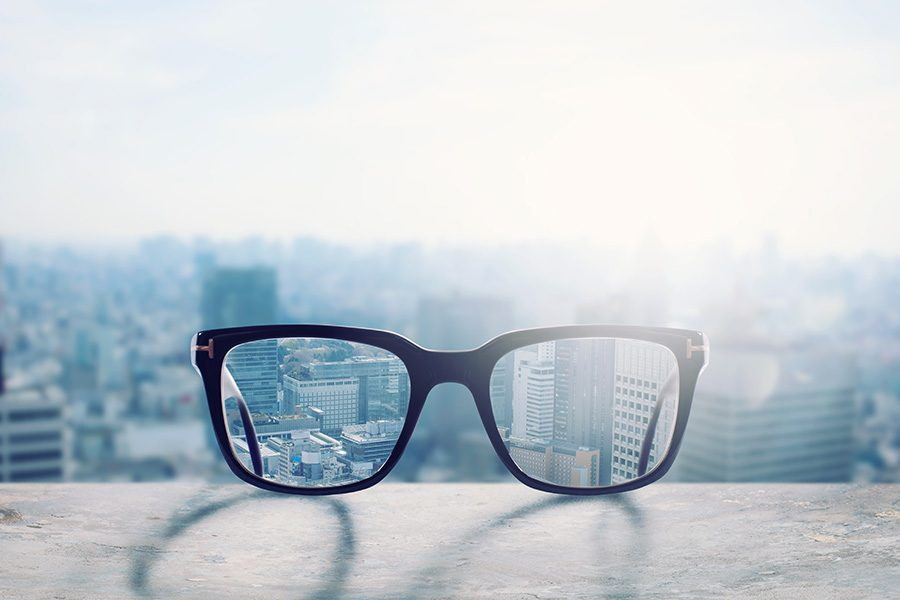 Group Vision Insurance - View of Glasses Laying on a Ledge with a Blurred City Background