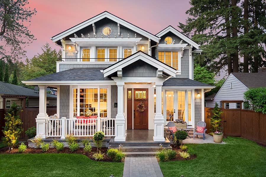 Home Insurance - View of Beautiful Two Story Home Exterior at Sunset with a Colorful Sky and Green Landscaping