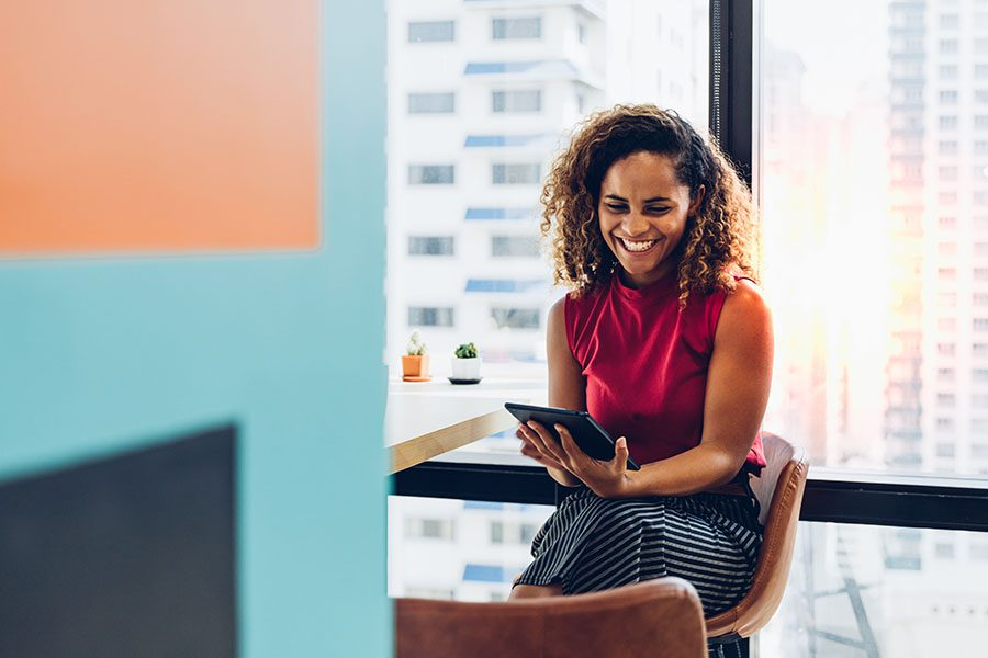 Report a Claim - Portrait of a Smiling Young Business Woman Sitting in a Modern Office While Using a Tablet with Views of the City Through the Windows