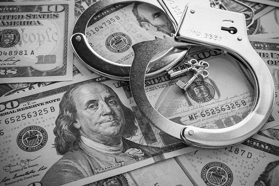 Crime Insurance - View of Handcuffs with Keys Laying on Top of Money