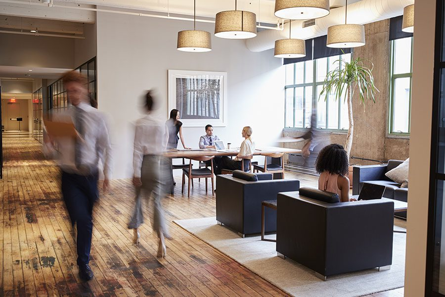 Employee Benefits - Interior View of a Modern Office Building Waiting Room with Blurred Business People Walking Through