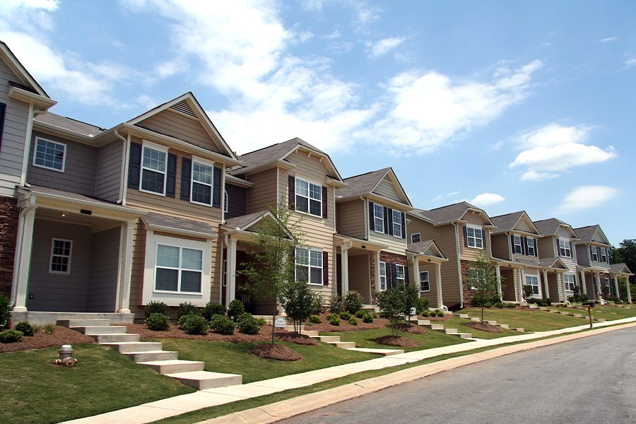 Homeowners Association Insurance - A Row of Newly Constructed and Professionally Landscaped Townhomes on a Bight Sunny Day