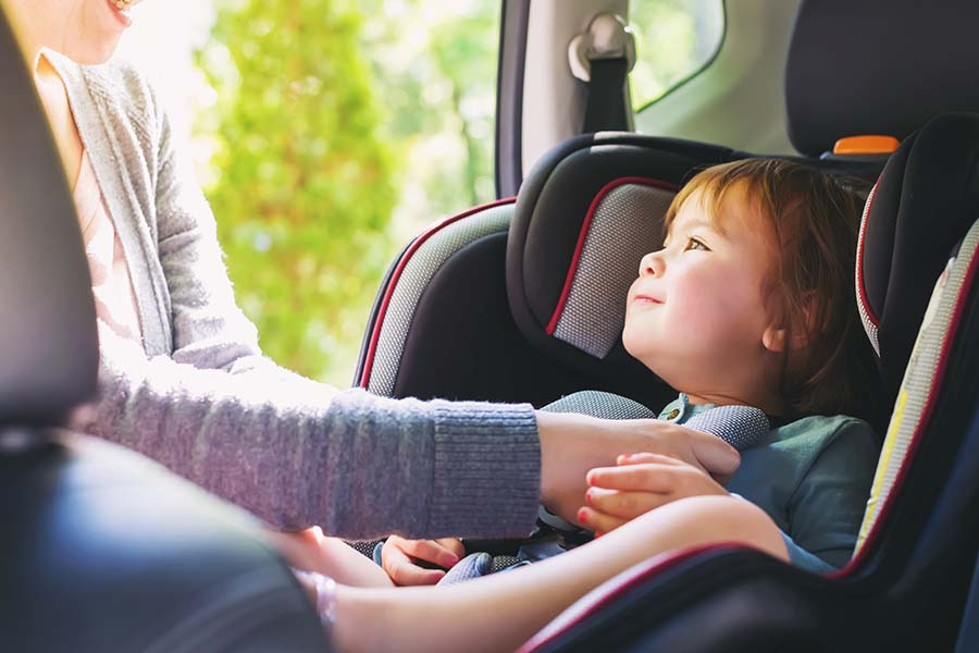 Blog - Young Toddler Girl Being Placed in Her Car Seat