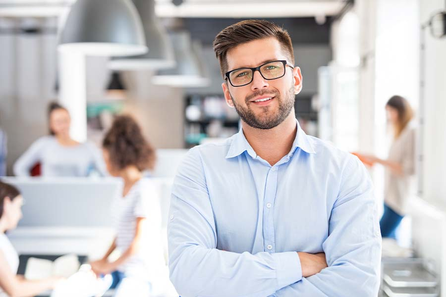 Business Insurance - Business Portrait of Young Confident Man Stanidng with Arms Crossed in the Office