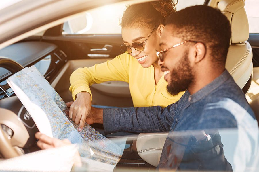 Blog - Young Couple Looking at a Map in Their Car Before Starting a Road Trip
