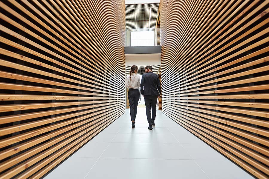About Our Agency - Rear View of Two Business Colleagues Walking Down a Hallway in a Modern Office with Wooden Panels on the Walls