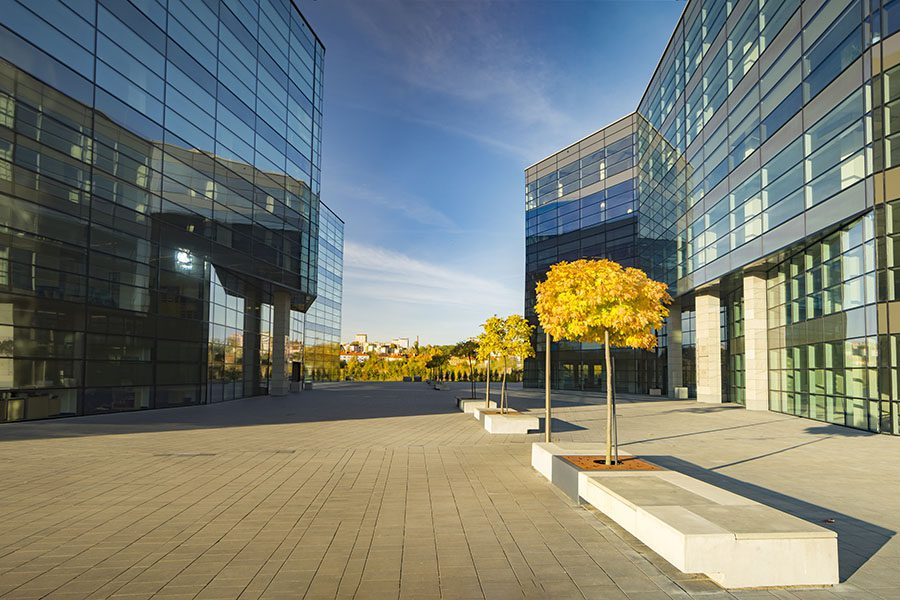 Insurance Quote - View of Two Commercial Office Buildings Next to a Paved Walkway in the City at Sunset