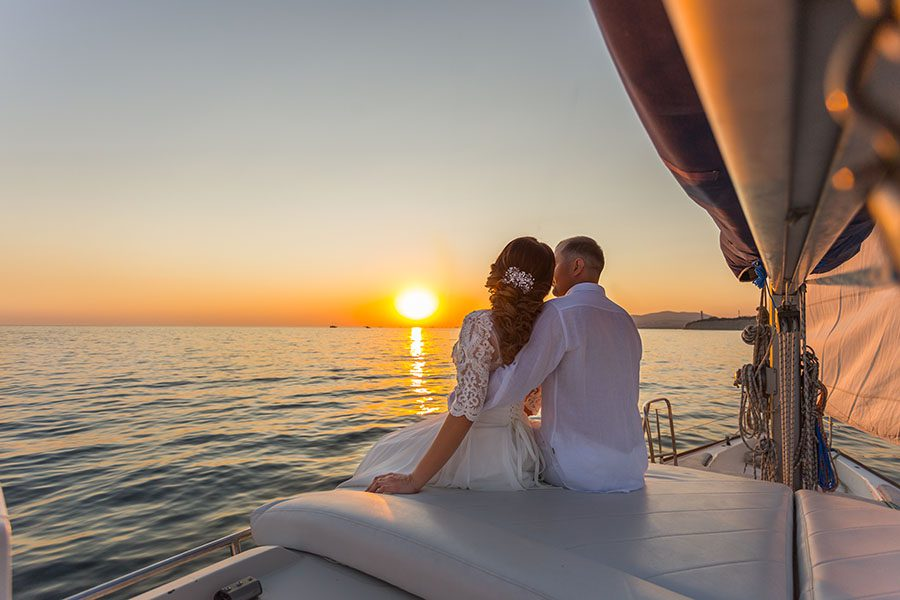 Personal Insurance - Portrait of a Newly Married Couple Sitting on a Yacht Enjoying the View of the Ocean and the Sunset