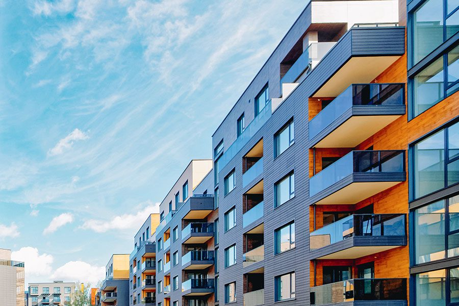 Specialized Business Insurance - View of a Modern Apartment Building Complex Against a Blue Cloudy Sky on a Sunny Day