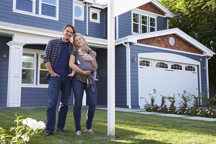 Personal Insurance - Young Smiling Parents Holding a Baby Standing in Front of Their New Two Story Home