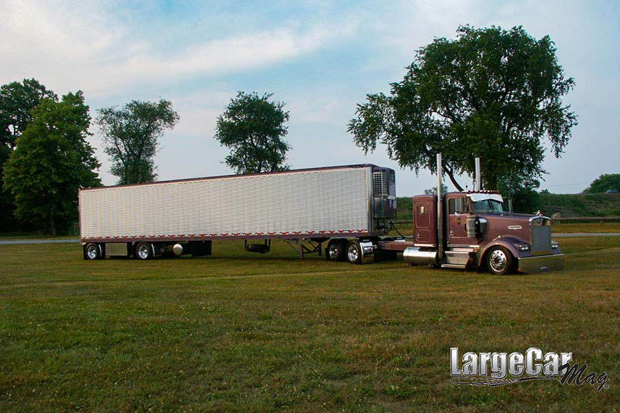 Transportation Resources - View of Large Red Truck with Trailer Parked on the Green Grass in an Open Field