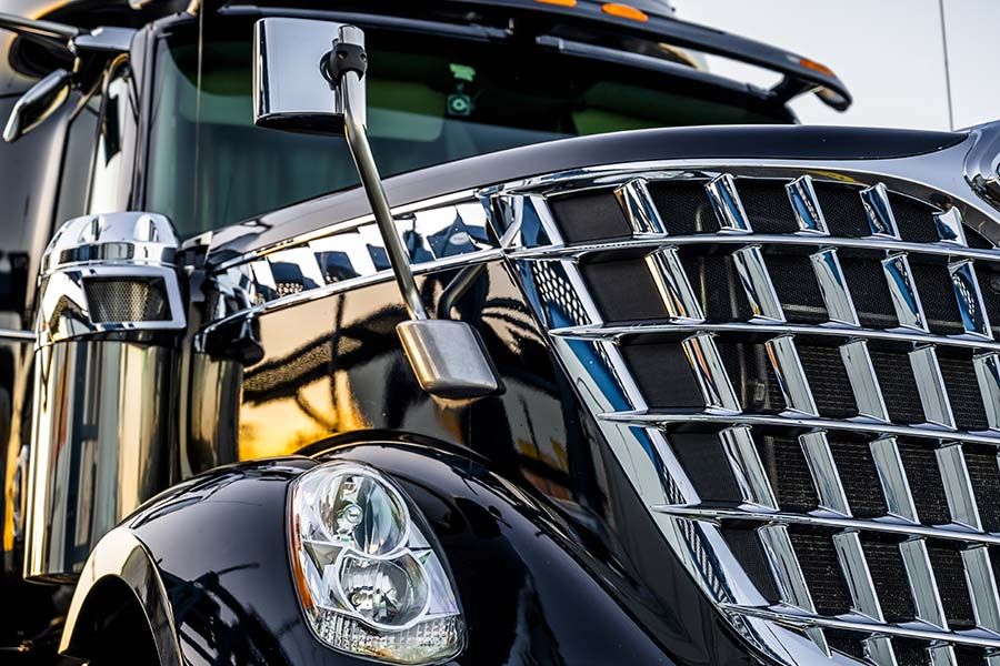 About Our Agency - Closeup View of the Front of a New Modern Black Truck with Shiny Chrome Grille