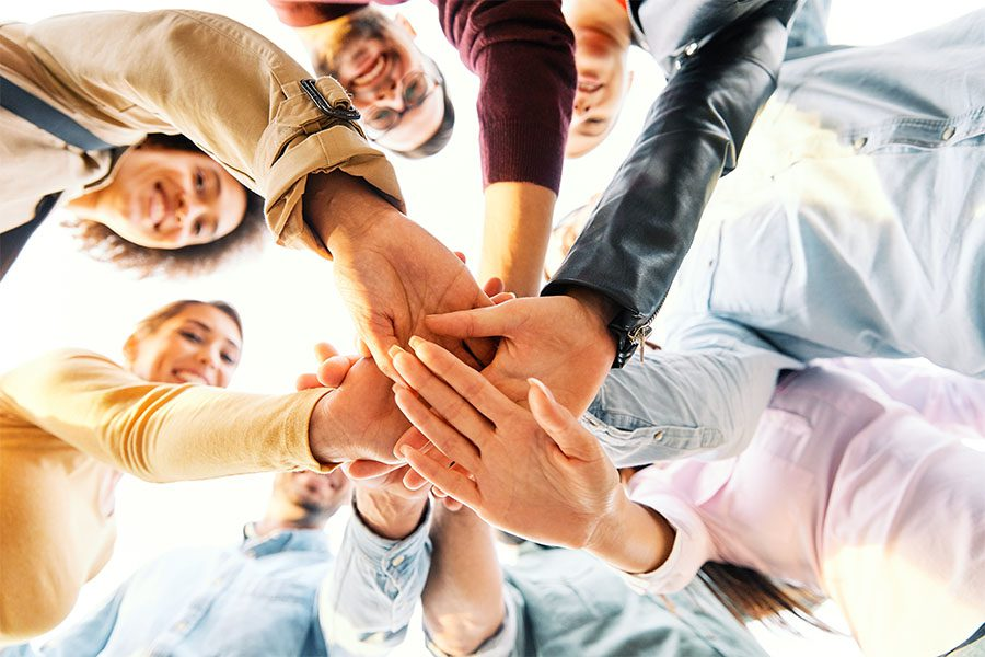 Doing Good - View of a Group of Smiling Friends Putting Their Hands Together While Standing Outside in a Unity Concept