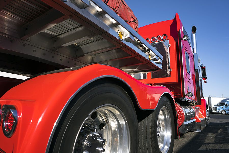 Insurance Companies - Side View of a Modern Red Truck with a Trailer Red in a Parking Lot