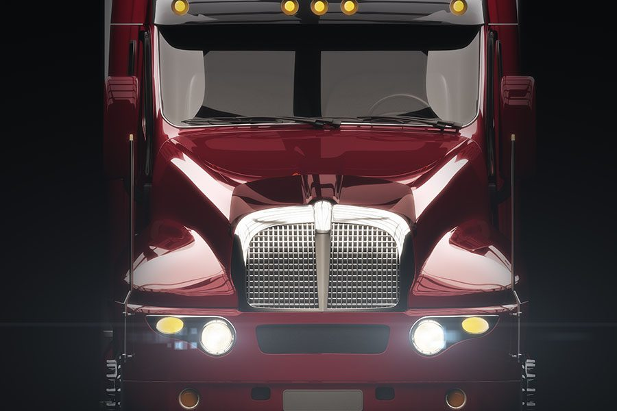 Join Our Team - Closeup View of Red Modern Truck with Front Headlights On Against a Black Background