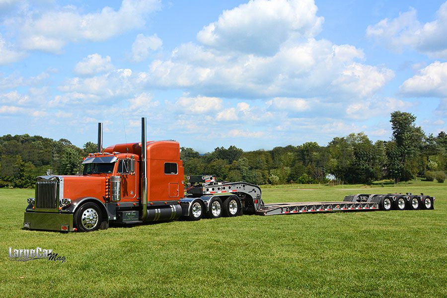 Specialized Business - View of a Red Semi Truck with a Tractor Trailer Parked on Green Grass Against a Blue Sky