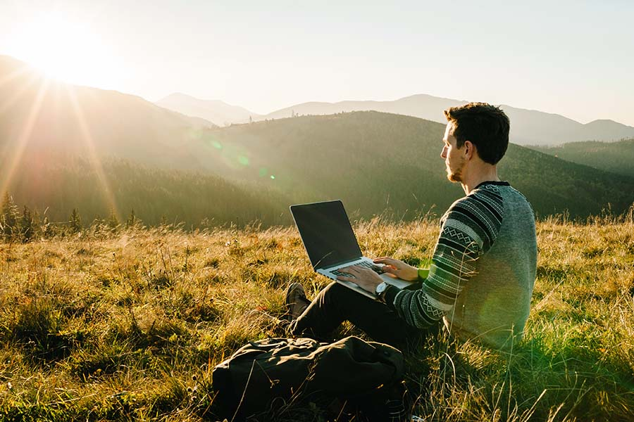 Blog - Portrait of a Young Man Sitting on the Grass Using a Laptop While on a Hike in the Mountains at Sunset
