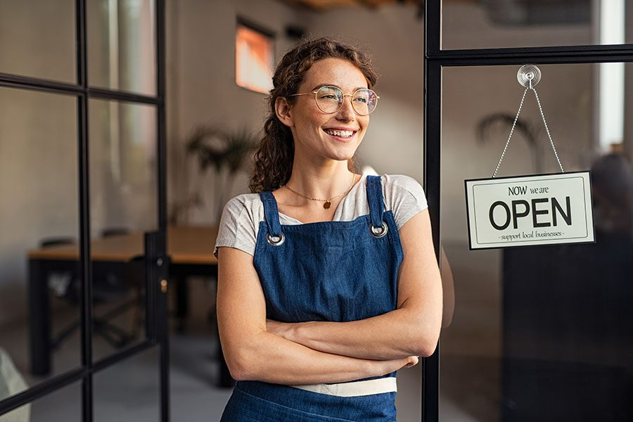 Business Insurance - Closeup Portrait of a Cheerful Young Business Owner Standing Outside Her Store Next to an Open Sign