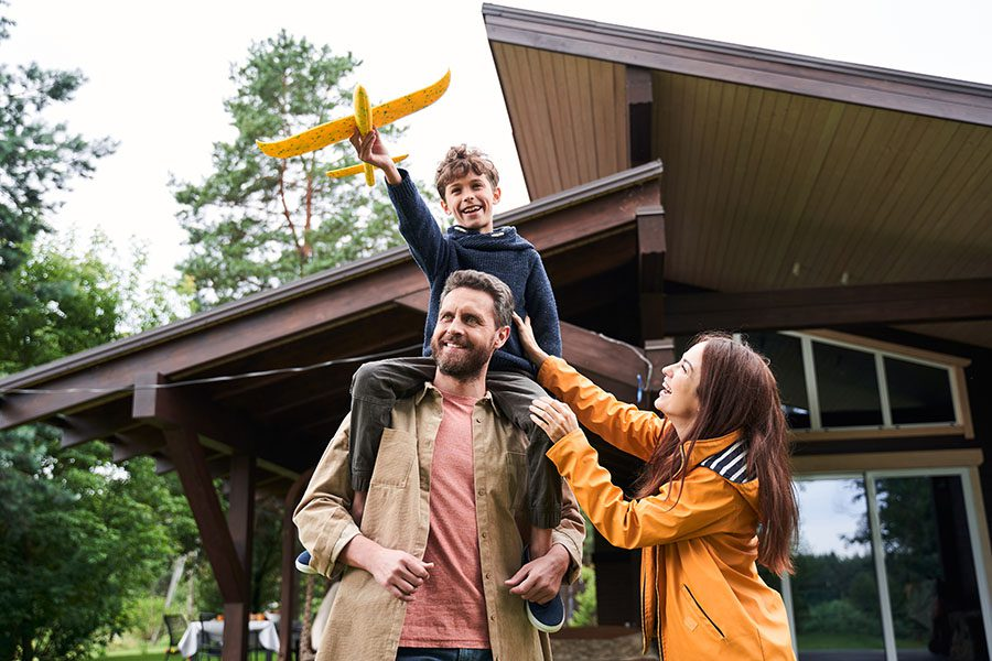 Personal Insurance - Portrait of a Happy Family Standing Outside Their Home While Playing with Their Son Who is Holding a Toy Airplane