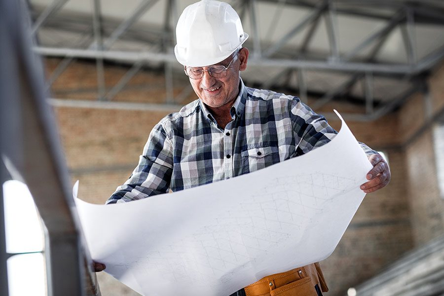 Specialized Business Insurance - Portrait of a Smiling Mature Contractor Standing Inside a New Building Construction Worksite While Looking at Building Blueprints