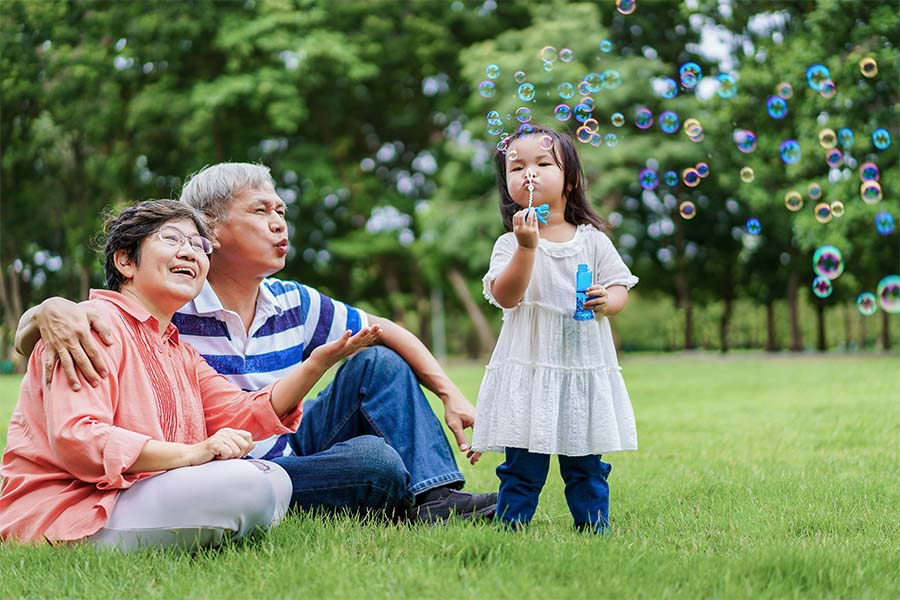 About Our Agency - Portrait of Smiling Grandparents Sitting on the Green Grass in the Park as They Watch Their Young Granddaughter Blow Bubbles