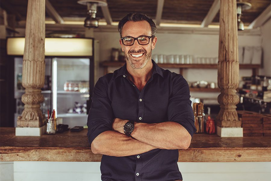 Business Insurance - Portrait of a Mature Smilng Business Owner Standing in His Coffee Shop with His Arms Folded