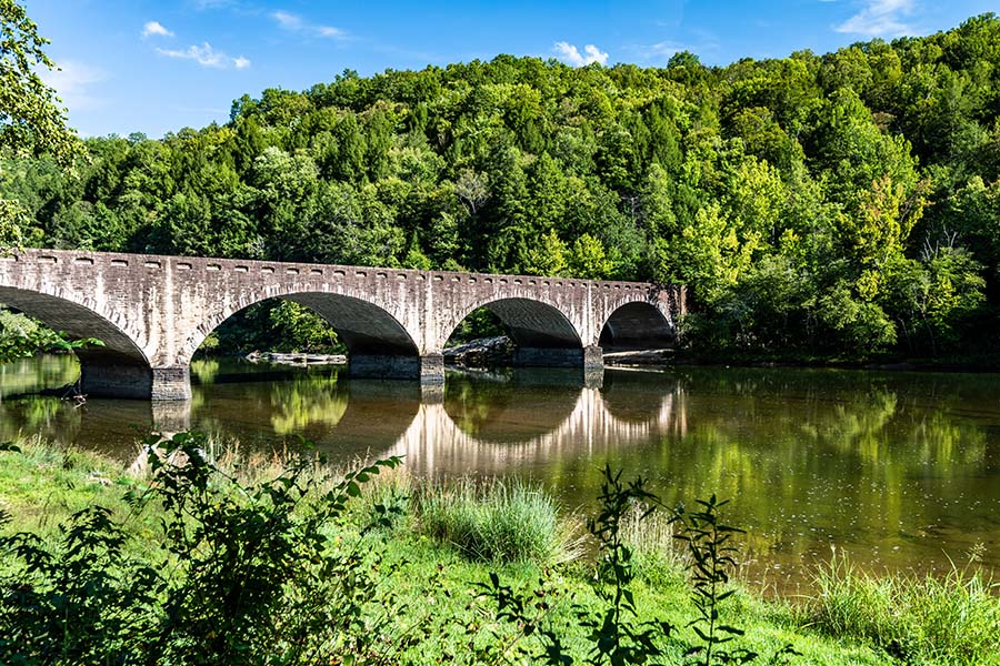 Contact - Scenic View of a River with a Bridge Across Next to Bright Green Trees in Cumberland Park Kentucky