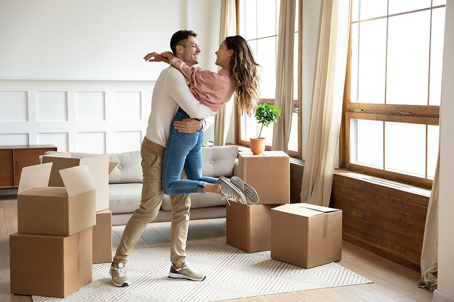 Insurance Quote - Portrait of a Joyful Couple Celebrating Their Move to Their New Apartment with Views of Moving Boxes All Around the Living Room