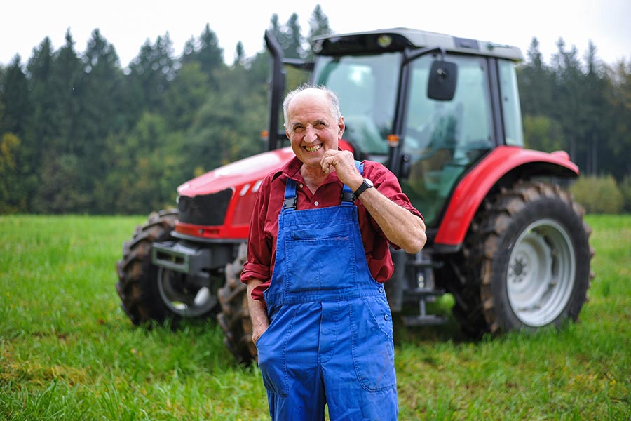 Business Insurance - Farmer Smiles and Poses in Front of His Tractor in a Green Field, Wearing Red Shirt and Blue Overalls