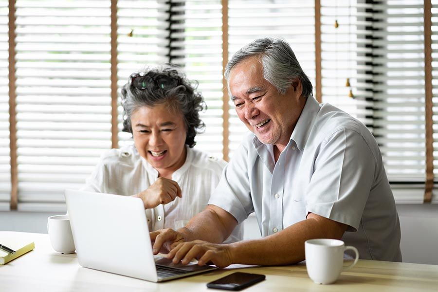 Client Center - Senior Couple Laughs as They Use a Laptop at Their Kitchen Table, Coffee and Cell Phone Nearby
