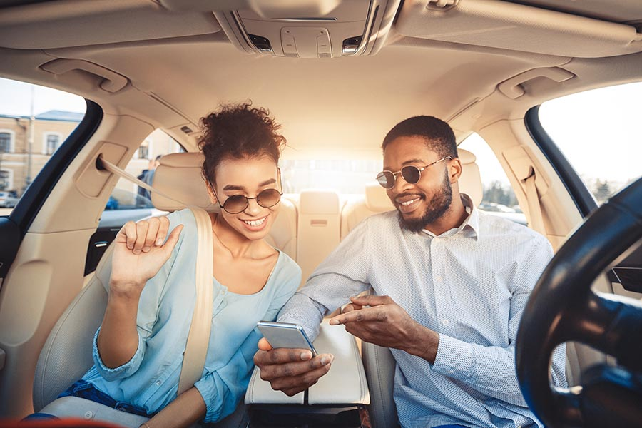 Contact Us - Happy Young Couple in a Nice Car Wearing Sunglasses, Both Looking at the Husband's Phone