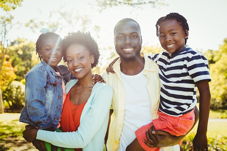Personal Insurance - Mother and Father Hold Their Two Young Kids, Smiling and Standing Together in Their Backyard