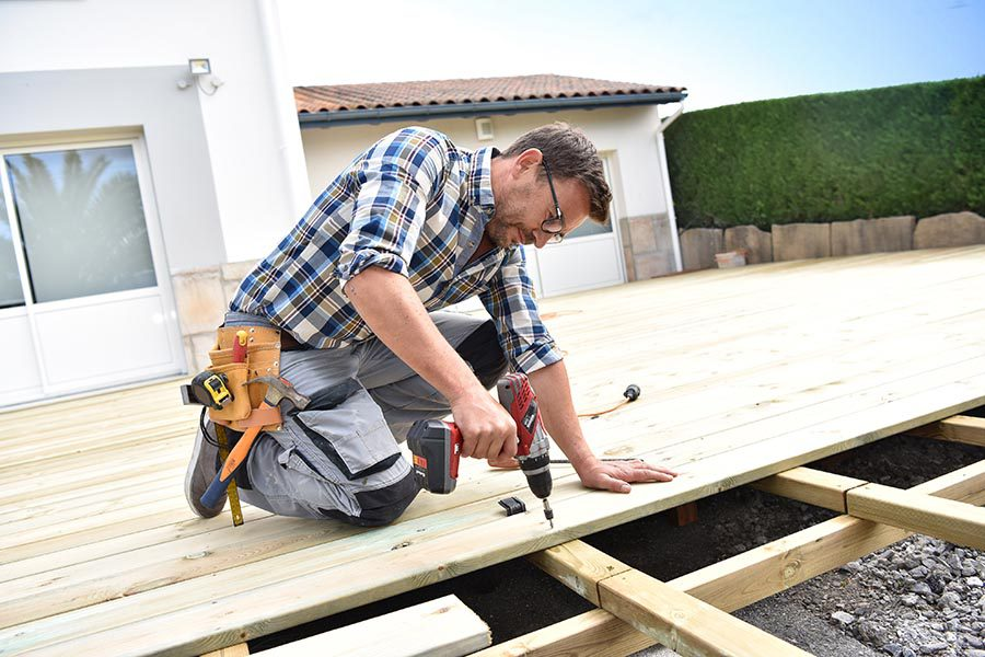 Specialized Business Insurance - Contractor in Jeans and Flannel Builds a Deck Onto a Home on a Sunny Day