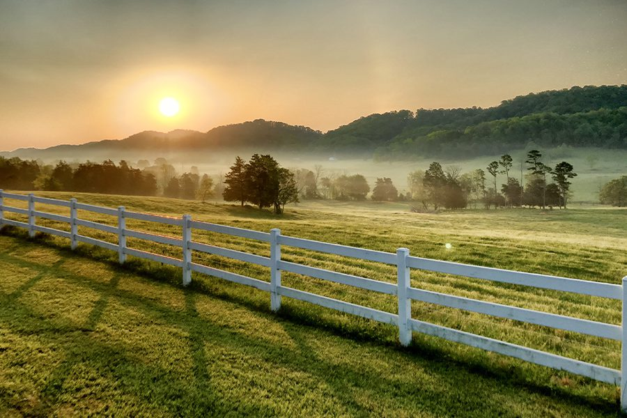Pasture, Rangeland, Forage Insurance - Sunrise Over Pasture and a White Fence with Trees and Hills in the Background