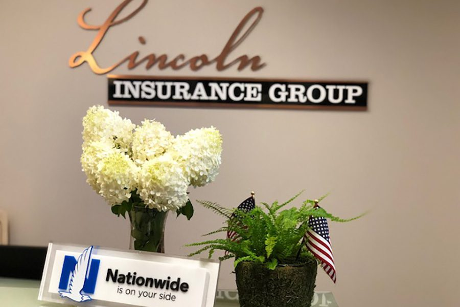 About Our Agency - Closeup View of Reception Area at Lincoln Insurance Group Office with Large Logo on the Wall and Flowers on the Front Desk