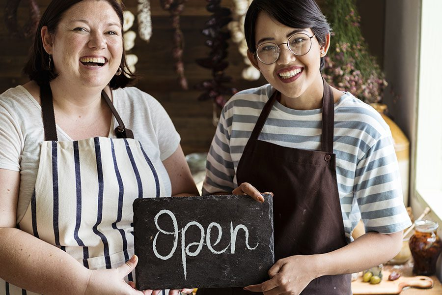 Business Insurance - Portrait of Two Cheerful Business Owners Standing in Their Shop and Holding Up an Open Sign