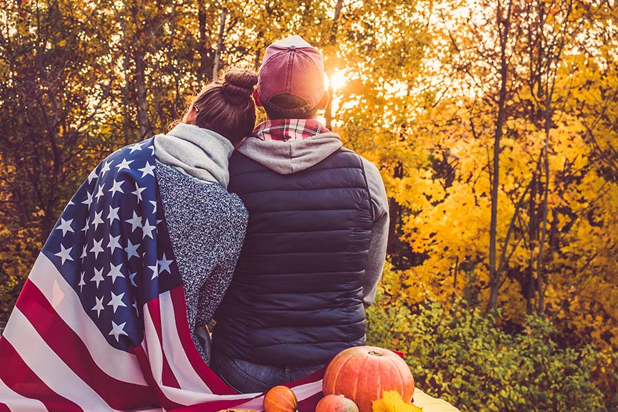 Client Center - Rear View of a Young Couple Sitting Together with an American Flag in the Park While Looking Out at the Sunset Through the Trees