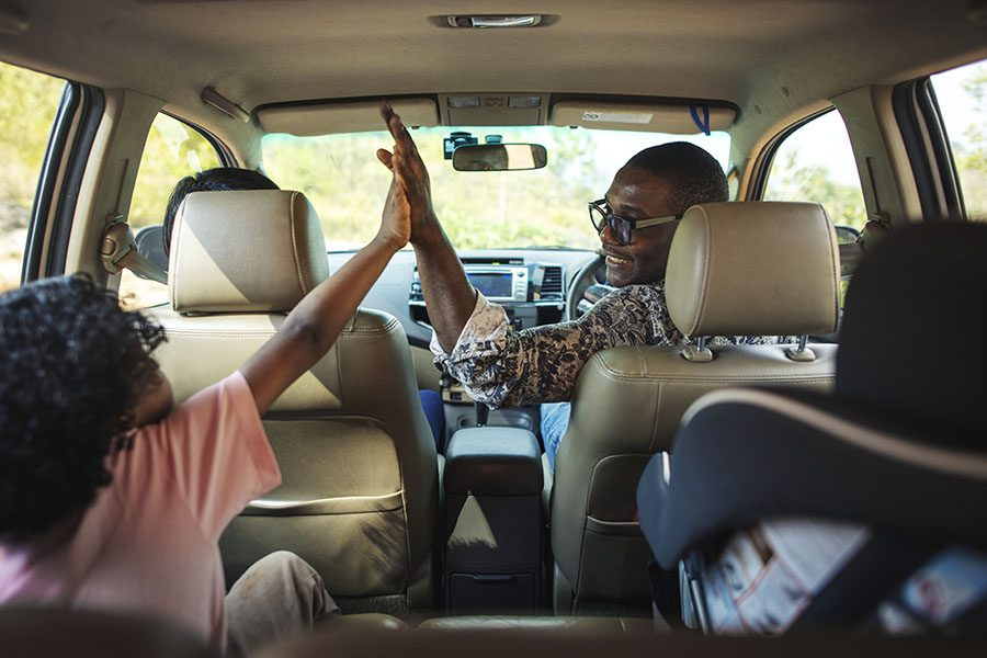 Personal Insurance - View of a Cheerful Father Giving His Daughter High Five as They Sit in a Car During a Road Trip